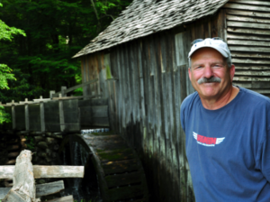 Man wearing a white baseball cap standing next to a wood shed