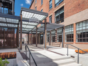 Steel framed entry canopy with red-orange brick warehouse in background