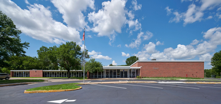 Single story midcentury school, red-orange brick and large windows