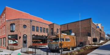Exterior corner view with food truck on patio in foreground and red-brown brick two story building in background